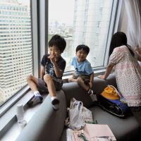 Making the best of it: Matsuki Kamoshita (left) and his brother Haruki play while their mother looks out the window in a room at the Grand Prince Hotel Akasaka in Tokyo on June 30, when hundreds of evacuees were preparing to leave for public housing units and other lodging. | KYODO