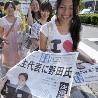 Read all about it: Women pick up copies of an extra edition printed by the Sankei Shimbun in Osaka on Monday after Yoshihiko Noda secured his ascent to prime minister earlier in the day. | KYODO PHOTO