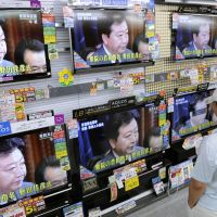 The same program: A shopper at an electronics store in Tokyo watches Yoshihiko Noda being voted in as the new prime minister at the Diet on Tuesday. | KYODO