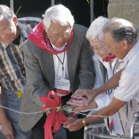 Cut free: Norman Mineta (left), an ex-internee who later served as U.S. transportation secretary, looks on as fellow internees cut a 'ribbon' of barbed wire at the Aug. 20 opening ceremony for the Heart Mountain Interpretive Learning Center in Wyoming. | KYODO PHOTO