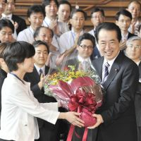 No regrets: Departing Prime Minister Naoto Kan receives a bouquet from his office staff as he leaves his official residence Friday. | AP