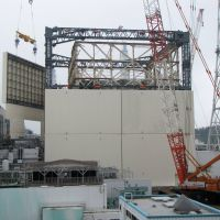 Eye-washing: A crane lifts a panel into place Thursday at the remnants of the No. 1 reactor building at the Fukushima No. 1 power plant. Tepco is putting a giant cover over the building ? one of two ripped apart by violent hydrogen explosions early in the crisis? to contain its radioactive emissions. The enclosure is expected to be completed by the end of October. | AP