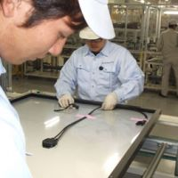 Finishing touches: Workers process solar panels on the assembly line in Solar Frontier's Miyazaki Prefecture plant.