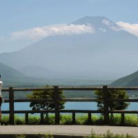 Grand tour: Tourists stand on the edge of Lake Motosu in Minobu, Yamanashi Prefecture, in July, with Mount Fuji in the background. | KYODO PHOTO