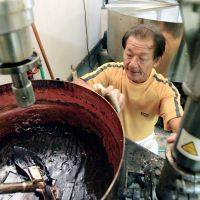 Candy man: Akira Hatashita, president of traditional candy maker Fudarakuya Co., cleans production equipment Tuesday at a factory in typhoon-ravaged Nachikatsuura, Wakayama Prefecture. | KYODO