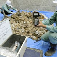 Put to the test: Workers check the radiation levels of tsunami debris from Iwate Prefecture that arrived in Tokyo on Thursday morning. Officials said the results were well below the legal limit of 0.01 microsievert per hour. | KYODO PHOTO