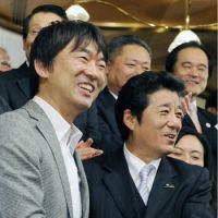 Winners: Toru Hashimoto (left) and Ichiro Matsui celebrate their successful campaigns Sunday. | KYODO PHOTO