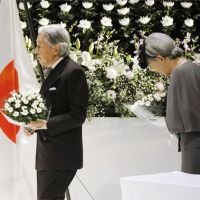 Honoring the fallen: Emperor Akihito and Empress Michiko offer flowers Tuesday at a memorial service in Tokyo for firefighters who died on duty in the past year. | KYODO