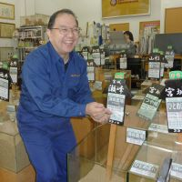 Toyozo Nishijima, who runs the Suzunobu rice shop in Tokyo, smiles as he holds some rice in his hands at the store. | KYODO PHOTO