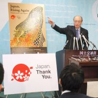 All welcome: Takeshi Maeda, minister of land, infrastructure, transport and tourism, unveils a new poster to promote inbound tourism by foreigners during a news conference at his ministry on Tuesday. | KYODO