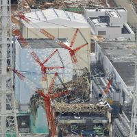 Closer view: Reactors 1 through 4 are viewed from a helicopter Sunday about 3 km away from the Fukushima No. 1 power plant. The no-fly zone over the plant was reduced to a radius of 3 km at midnight Friday. | KYODO