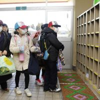 Comfortable fit: Students at Ishigami No. 1 Elementary School in Minamisoma, Fukushima Prefecture, check their shoe cabinet as they enter the school for the first time in nearly a year on Monday. | KYODO