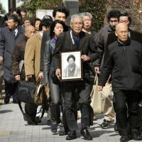 Long march: Akio Mizoguchi enters the Fukuoka High Court on Monday carrying a photo of his mother, Chie Mizoguchi, who was posthumously recognized by the court as a victim of the Minamata mercury poisoning later the same day. | KYODO