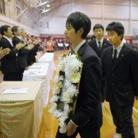 Rite of passage: Carrying a picture of one of 12 classmates killed in the quake-tsunami disaster last year, a Takata High School student leaves his graduation ceremony Thursday. Takata High, located in Rikuzentakata, Iwate Prefecture, moved to an empty school building in the neighboring city of Ofunato, where the ceremony was also held. | KYODO