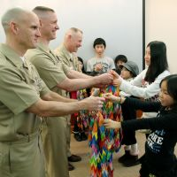 Friends: Evacuees hand paper cranes to U.S. servicemen Feb. 24 at the U.S. Navy base in Yokosuka, Kanagawa Prefecture. The cranes, made by 650 evacuees from Minamisoma, Fukushima Prefecture, contain messages of thanks for Operation Tomodachi. | KYODO