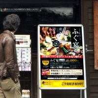 Fugu for all: A man passes a sign advertising fugu meals outside a restaurant in Minato Ward, Tokyo, on Thursday. | YOSHIAKI MIURA