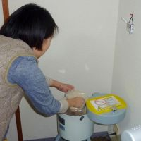 Home-made: A woman measures out rice bran to test it for radioactivity in Yokohama on Monday. | KYODO