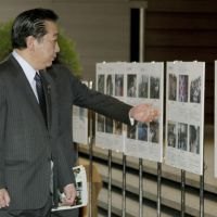 Always in mind: Prime Minister Yoshihiko Noda looks at photos displayed at an exhibition titled 'Watashi no Fukko Dayori' (My Reconstruction Letter') at the entrance to the Prime Minister's Office on Monday. | KYODO