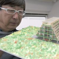Solutions: Toyo Ito of Toyo Ito & Associates, Architects, looks at a model of his redevelopment project that is being examined by the city of Kamaishi, in Iwate Prefecture, at his Tokyo office on Feb. 22. | ROB GILHOOLY PHOTOS