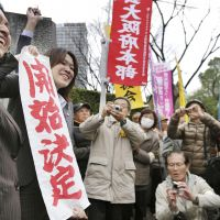 Banner day: Lawyers for Keiko Aoki and Tatsuhiro Boku unfurl a sign that reads the Osaka District Court has decided to grant their clients a retrial. | KYODO