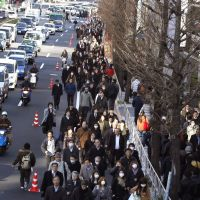 Walk the line: Commuters walk on a Tokyo street last March 12. The Great East Japan Earthquake that struck Tohoku the previous day disrupted train services for several days. | AP