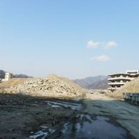 Tsunami-scape: Piles of debris mask the abandoned buildings of Kamaishi East Junior High School (right) and Unosumai Elementary School in Kamaishi, Iwate Prefecture, on Feb. 21. | SETSUKO KAMIYA PHOTOS