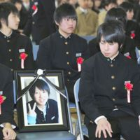 Poignant: A student at Aoba Junior High School in Ishinomaki, Miyagi Prefecture, looks at the photo of a dead classmate during a graduation ceremony Saturday. | KYODO