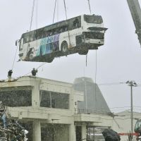 A bus swept onto a community center's rooftop is finally lifted off in Ishinomaki, Miyagi Prefecture. | KYODO