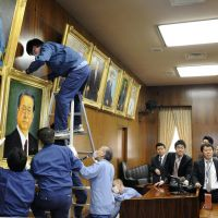 Larger than life: Democratic Party of Japan kingpin Ichiro Ozawa watches workers hang his portrait in a Lower House facility Monday. | KYODO