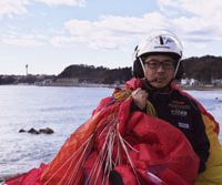 Coastal chronicler: Eiji Sakai carries his paragliding gear in Iwaki, Fukushima Prefecture, last December. | EIJI SAKAI