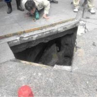 Hidden menace: A man looks into a sinkhole that formed beneath a sidewalk in Naka Ward, Nagoya, in January. | NAGOYA CITY WATERWORKS AND SEWERAGE BUREAU