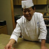 Cuisine for a cause: Yoshihiro Murata, president and head chef at Michelin three-star restaurant Kikunoi in Kyoto, serves 'hassun,' one of the dishes of 'kaiseki' haute cuisine, at the restaurant's Tokyo branch Feb. 17. | KYODO
