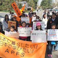 Fighting to stay: Foreigners who have overstayed their visas rally Monday in Tokyo's Hibiya district, calling for the Justice Ministry to grant them special residency permits. | YOSHIAKI MIURA