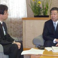Unconvinced: Kyoto Gov. Keiji Yamada (right) is briefed Thursday by an official from the Nuclear and Industrial Safety Agency in Kyoto about the result of stress tests on Kansai Electric Power Co.'s Oi nuclear plant in Fukui Prefecture. | KYODO