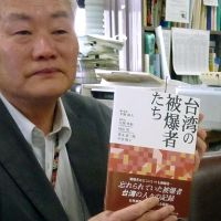 Witness: Nobuto Hirano, a representative of a Nagasaki-based liaison group for atomic bomb survivors overseas, holds a recently published book containing testimonies by Taiwanese survivors at Nagasaki City Hall. | KYODO