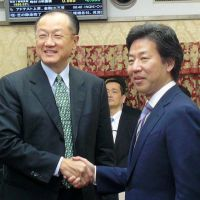 Grip and grin: Finance Minister Jun Azumi poses Sunday with visiting World Bank presidential candidate Jim Yong Kim at the ministry. | KYODO