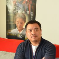 Fast forward: Chinese director Jiang Qinmin is interviewed Sunday at his Beijing studio with a poster of his latest film, 'Tokyo Newcomer,' behind him. | KYODO