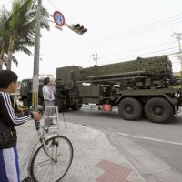 Just in case: A boy looks on as a Self-Defense Forces truck with Patriot Advanced Capability-3 interceptor missiles passes by in Ishigaki, Okinawa Prefecture, on Thursday morning. | KYODO