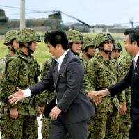 Thin khaki line: Ishigaki Mayor Yoshitaka Nakayama (left) and Taketomi Mayor Eicho Kawamitsu greet Self-Defense Forces members Friday after inspecting a PAC-3 battery deployed on Ishigaki Island in Okinawa Prefecture, ahead of North Korea's planned missile launch. | KYODO