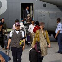 Japanese tourists walk toward a bus Sunday after being airlifted to Chaklala airbase in Rawalpindi, Pakistan. About 120 foreign tourists, mostly from Japan, were trapped in northern Pakistan due to sectarian violence.   AP PHOTO