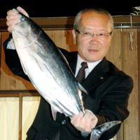 Vote catcher: Mayor Shigeo Ishihara of Omaezaki, Shizuoka Prefecture, holds up a bonito, one of the city's chief products, Sunday night after winning his third term as mayor. | KYODO