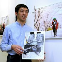 High point: Tomohiko Yoshida visits his photo exhibition on Narao Higashiura, who set a record by ascending mountains for nearly 10,000 days in a row, in Nagoya this month. | CHUNICHI SHIMBUN