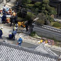Crime scene: Police investigate the site of a car crash in Kameoka, Kyoto Prefecture, where an 18-year-old driver smashed into a group of elementary schoolchildren, killing a student and a mother who was accompanying them on Monday. | KYODO