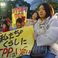 Trade off: A protester holds a sign reading 'We don't need the TPP in our lives' during a Wednesday rally in Tokyo's Hibiya Park to protest Japan's bid to enter the Trans-Pacific Partnership free-trade accord talks. | KYODO