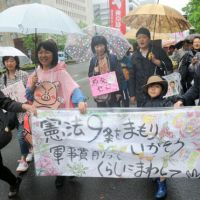 Taking a stance: Citizens stage a Thursday march in Tokyo against moves to revise the Constitution, walking from Hibiya Park to the Ginza district. About 2,700 people gathered at the park, where politicians from the Social Democratic Party and the Japanese Communist Party made speeches. | SATOKO KAWASAKI