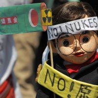 With one voice: A demonstrator holds a dummy wearing antinuclear signs at a rally against atomic energy in Tokyo Saturday. | AP