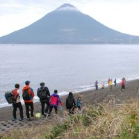Walk in the park: Hikers walk on an 'olle' trail in Ibusuki, Kagoshima Prefecture, as Mount Kaimondake looms in the background. The trail is one of four such routes in Kyushu. | JIJI