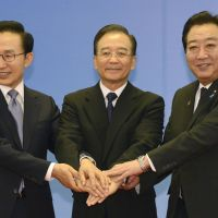Three's company: South Korean President Lee Myung Bak, Chinese Premier Wen Jiabao and Prime Minister Yoshihiko Noda join hands before their summit on security and economic issues in Beijing on Sunday. | KYODO