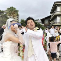Takahisa Yamaguchi and his bride, Mai, look at the annular solar eclipse during their wedding at a hotel in Ibusuki, Kagoshima Prefecture, on Monday. | KYODO