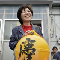 Sakiko Miura holds a returned fish farm float Wednesday that had been swept away when the March 2011 tsunami destroyed her eatery in Minamisanriku, Miyagi Prefecture, only later to turn up on an island off Alaska. | KYODO